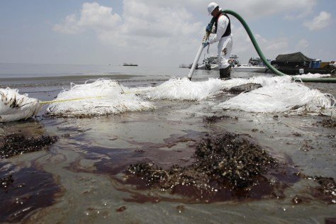 Image: A worker uses a suction hose to remove oil washed ashore from the Deepwater Horizon spill in Belle Terre, La..