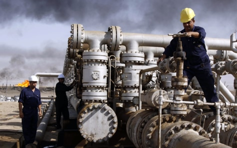 Image: Iraqi workers at the Rumaila oil refinery