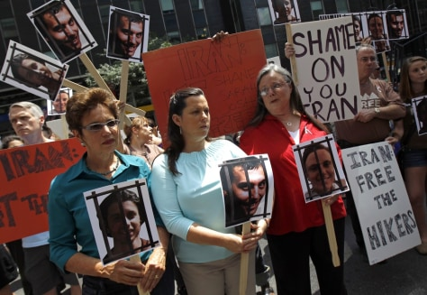 Image: Fattal, Hickey and Shourd hold pictures of their children while protesting for their release with others outside the Iran Mission in New York