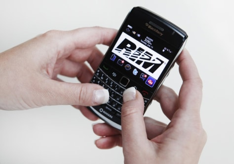 Image: A person poses while using a Blackberry Bold 2 smartphone