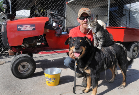 Image: Greg Pike, 50, of Bisbee, Ariz., poses with Booger the dog, Kitty the cat, and Mousey the rat, in front his souped-up riding lawnmower