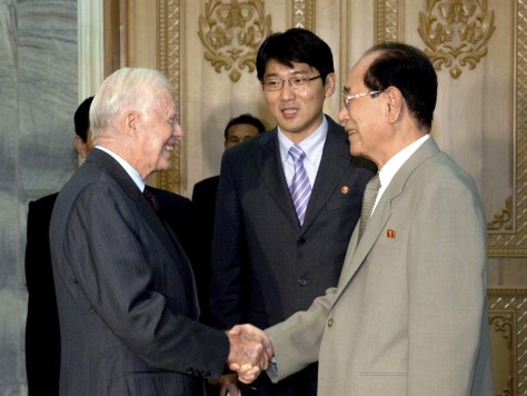 Image: Former U.S. President Carter shakes hands with Kim, president of the Presidium of the Supreme People's Assembly of North Korea, during their meeting at the Mansudae Assembly Hall in Pyongyang