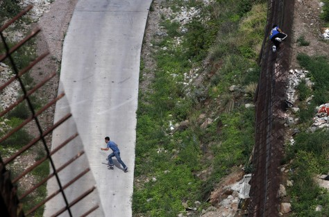 Image: Two men illegally cross the border fence separating Nogales, Ariz., and Nogales, Sonora, Mexico