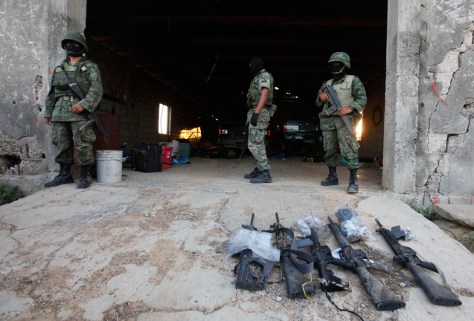 Image: Soldiers stand next to weapons seized at a warehouse after a gunfight with drug gang members at a ranch near Monterrey