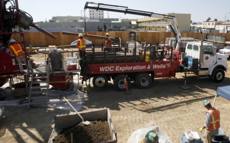 Image: Workers drill wells on Sept. 9