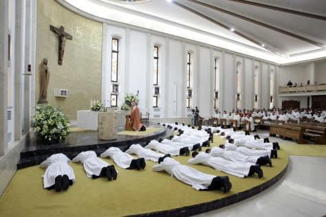 Image: New deacons prostrate in front of the altar during their ordination mass at the Legionaries of Christ center