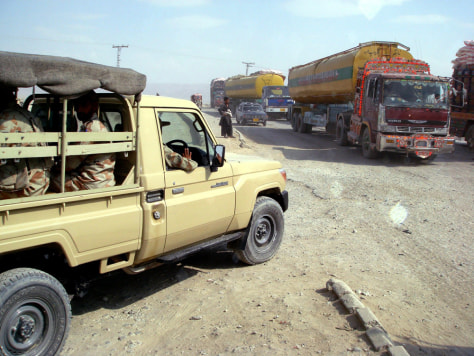 Image: Pakistani soldiers and NATO supply trucks