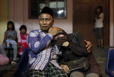 Image: Two colleagues of a train crash victim wait outside a hospital morgue in Pemalang in Indonesia's central Java province