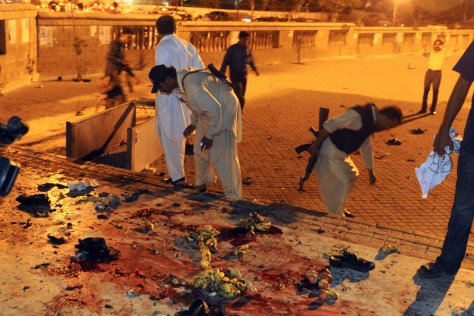 Image: Security personnel collect evidence from blast site after two bomb explosions at the entrance of the shrine to Sufi saint Abdullah Shah Ghazi in Karachi
