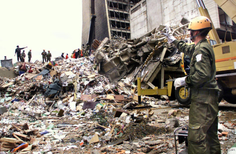 Workers stand on what remains of a building in front of the U.S. embassy in Nairobi, Kenya after the deadly 1998 bomb attack