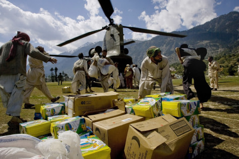 Image: Pakistani volunteers unload relief supplies from a U.S. Chinook helicopter