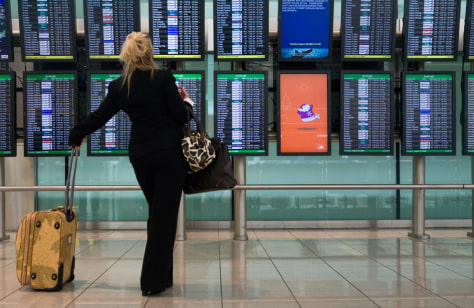 Image: A passenger looks at a flight monitor that shows numerous delayed and canceled flights at Baltimore/Washington International Thurgood Marshall Airport