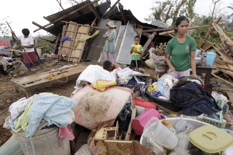 Image: Filipinos salvage their belongings after Typhoon Megi destroyed their house in Tumauini