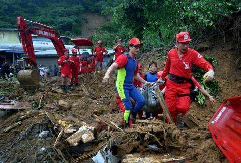 Image: Rescue workers remove a body from debris