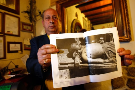 Image: Giuseppe Sciortino, nephew of the legendary Sicilian bandit Salvatore Giuliano, shows a picture of Giuliano's body in his house in Montelepre