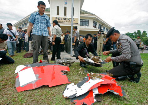 Image: Indonesian police officers inspect parts of a Qantas jetliner