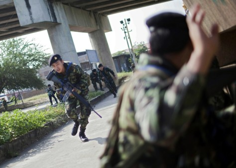 Image: Thai soldiers run for cover near the Thai-Myanmar border in Mae Sot