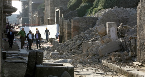 Image: People stand near debris after a house, once used by gladiators to train before combat, collapsed in Pompeii