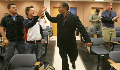 Image: Raymond Palacio, center, greets University of Texas at El Paso students Manuel Acosta, left, and Eder Diaz, second left