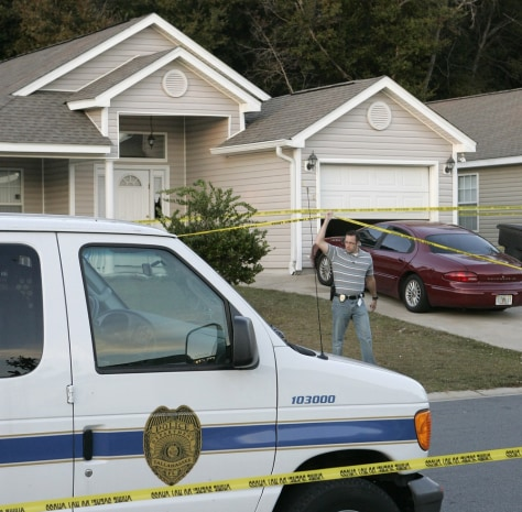 Image: A Tallahassee investigator lifts police tape to pass under at a home