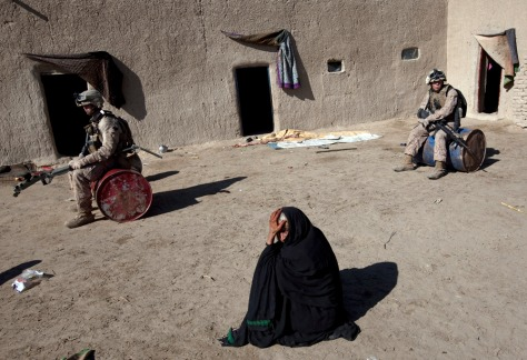 Image: An Afghan woman waits for Marines to search her home