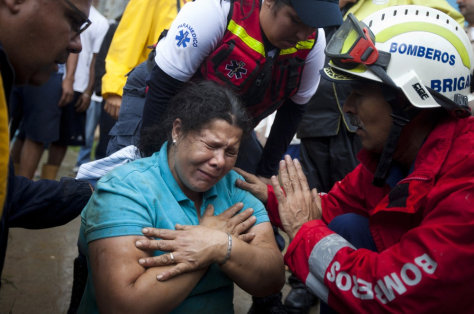 Image: A woman cries after being rescued from her house, which had collapsed during torrential rains, in Tamanaquito