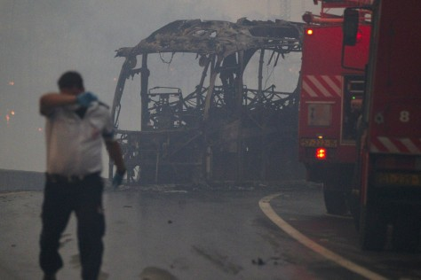 Image: An Israeli medic walks near a charred bu