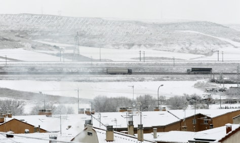 Image: Trucks drive on a highway in Burgos, northern Spain as the first snow of the season cloaks the city