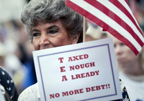 "Image: Tea Party supporter holds a sign that reads ""Taxed enough already."""
