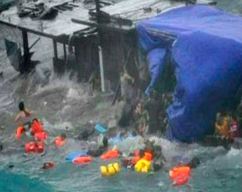 Image: A boat laden with refugees is driven onto rocks at Christmas Island in this still image taken from video