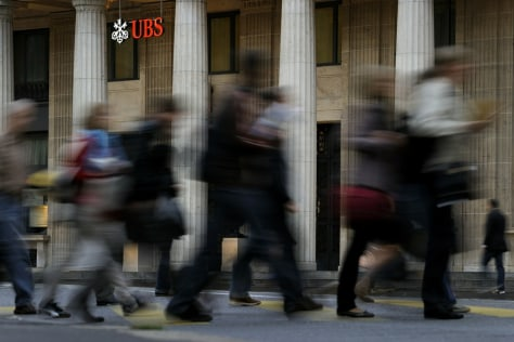 Image: Commuters walk past UBS