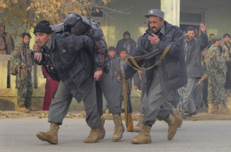 Image: A wounded Afghan policeman is carried away by his colleagues