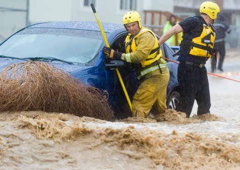 Image: San Bernardino County firefighters work their way towards a car trapped