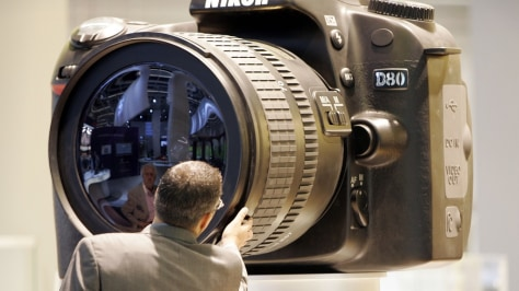 Image: man examines large model of a digital camera