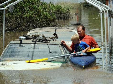 Image: Man, son kayak in flooded area