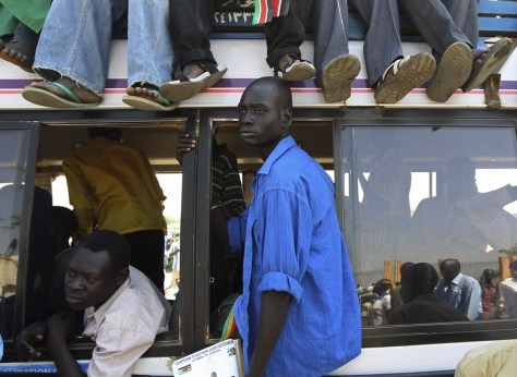Image: Men sit on a bus as they arrive for a rally in Juba