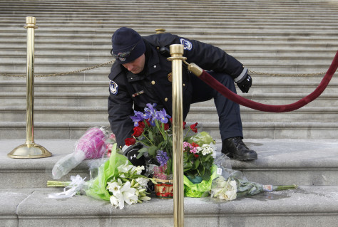 Image: A Capitol policeman arranges flowers placed on the steps of the U.S. Capitol for Arizona Congresswoman Gabrielle Giffords, in Washington