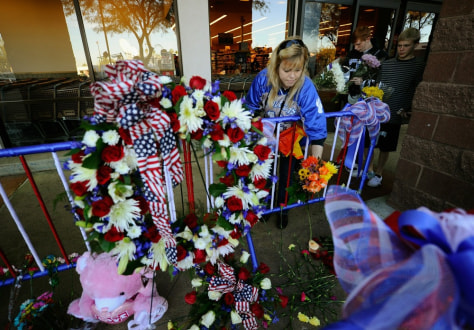 Image: Shelby Garner places a flower on a makeshift memorial