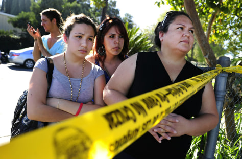 Image: Family members wait for their children after an accidental shooting at Gardena High School in Los Angeles.
