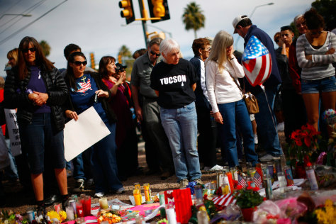 Image: People look at items left by well-wishers outside the office of U.S. Rep. Gabrielle Giffords in Tucson, Arizona