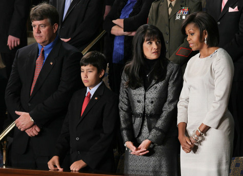 Image: First lady Michelle Obama talks Tuesday before the State of the Union speech to John, Dallas and Roxanna Green, the family of the late Christina Taylor Green