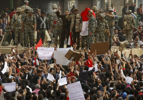 Image: A senior army officer salutes a crowd of cheering protesters at Tahrir square in Cairo