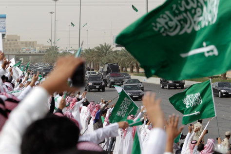 Image: Saudis wave and cheer to welcome the convoy of the King Abdullah of Saudi Arabia