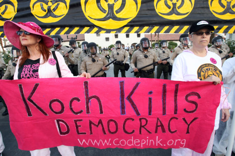 "Riverside County Sheriff's deputies in riot gear are seen behind Jodie Ivanes, of Venice Beach, Calif., left, and Ellen Sturtz, of West Los Angeles, right, during a protest dubbed the ""Koch Busters Rally."""