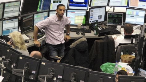 Image: Traders are pictured at their desks, with one looking left out of the daily grind.
