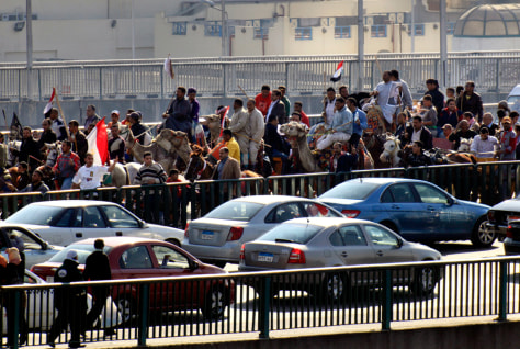 Image: Supporters of President Hosni Mubarak, some riding camels, march in Cairo