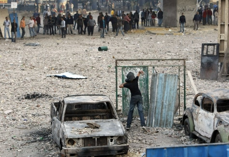 Image: Anti-government demonstrator throws a projectile at pro-regime opponents in Cairo