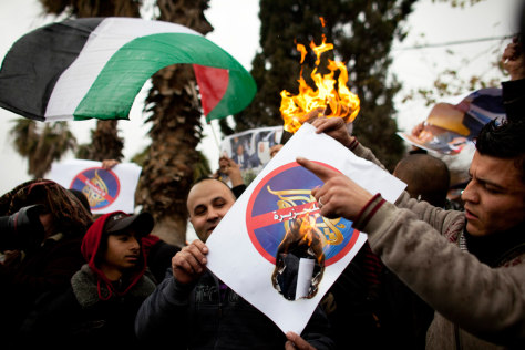 Image: Palestinians burn posters with the logo of Al-Jazeera TV station