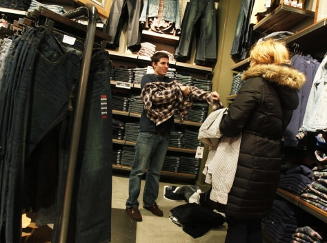 Image: A man tries on a shirt while shopping at a clothing store in New York