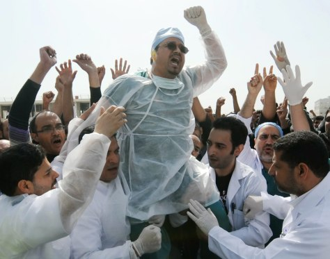 Image: Medical workers react to news that paramedic crews at protest were attacked by pollice in Bahrain